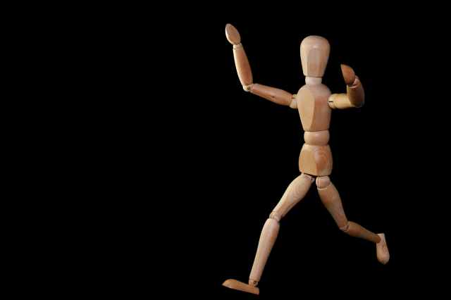 timelapse photography of brown wooden puppet running on a black screen